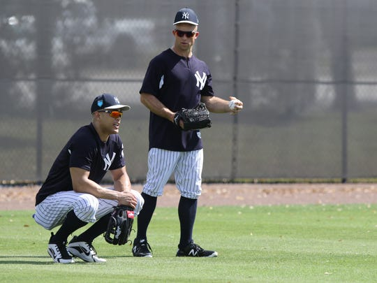 Giancarlo Stanton and Brett Gardner in the outfield fielding balls after they completed batting practice.