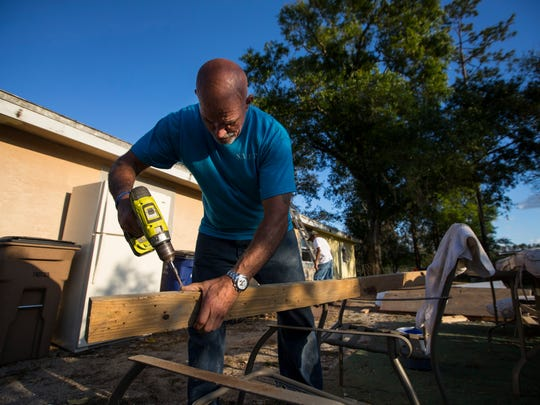 John Johnson removes screws from a used piece of lumber that will be reused as part of a house renovation in Fort Myers Tuesday, February 20. The St. Martin de Porres ministry is rehabbing the house which will provide temporary housing for a homeless family. Some of the workers participating in the restoration are also homeless and the project provides work, training and temporary housing for them.