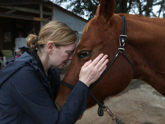Adrienne LaPointe embraces her horse YotaSoho at Mahan Farms on Friday, Feb. 9, 2018. LaPointe, who has been through 23 surgeries after two debilitating falls, has found working with YotaSoho helped pull her out of depression and changed her life.