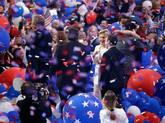 Democratic presidential nominee Hillary Clinton speaks with other people as balloons and confetti fall during the final day of the 2016 Democratic National Convention  in Philadelphia.