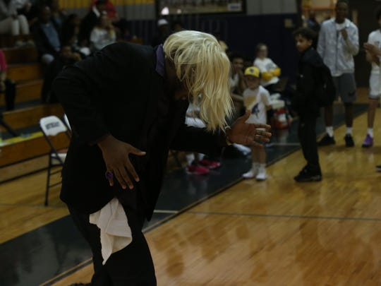 Northeast quarterback and basketball fan Heath Williams dances in his Ric Flair costume prior to the start of the Northeast-Wilson Central region tournament quarterfinal game Saturday night at Northeast High.