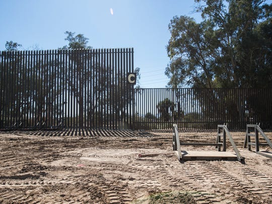 a metal barrier separating mexico and the us is being