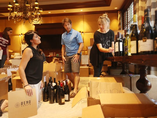 From second from left, Kristen Palazzo, David Collins and Melissa Cofta prepare for the Southwest Florida Wine & Food Fest at Quail West Golf & Country Club in Naples on Thursday.
