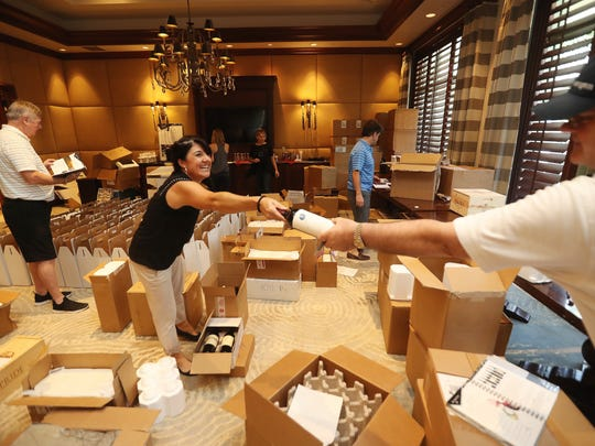 Kristen Palazzo, left,  and Bill Toler prepare for the Southwest Florida Wine & Food Fest at Quail West Golf and Country Club in Naples on Thursday 3/1/2018.