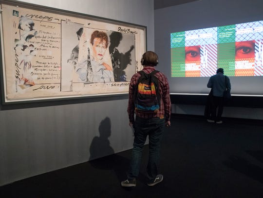 "A visitor inspects Edward Bell's ""Scary Monsters (and"