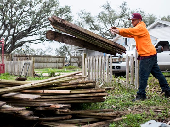 Jason Wright throws wood onto a pile of debris near the street for pickup on Thursday Feb.22, 2018 in Rockport. Wright was helping a friend clean up a damaged fence from Hurricane Harvey.