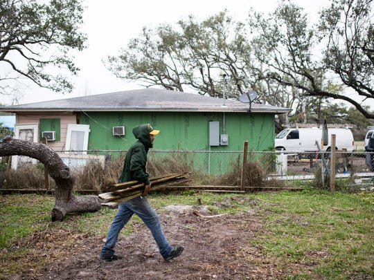 Alex Soliz  carries a pile of wood to the street for pickup on Thursday Feb.22, 2018 in Rockport. Soliz was helping a friend clean up a damaged fence from Hurricane Harvey.