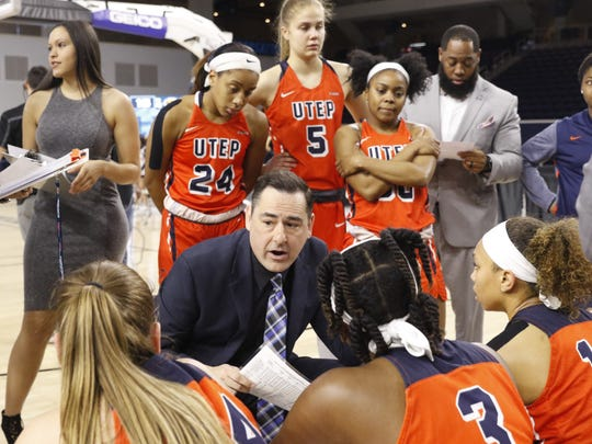 UTEP women's coach Kevin Baker talks strategy with the Miners during a timeout.