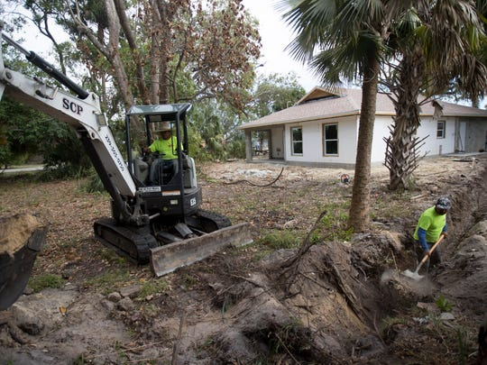 A crew  from SCP Enterprises digs an underground electric line that will lead to a new house being built by the company on South Street in Fort Myers.