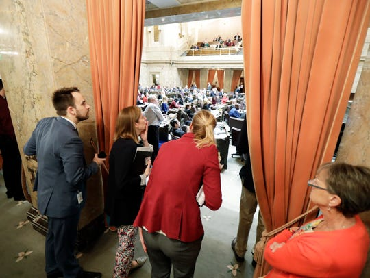 Legislative staffers watch from the wings of the House
