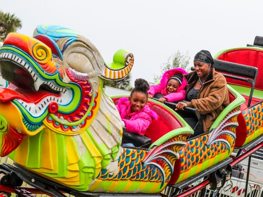 Diana Clarke of Lehigh rides the dragon roller coaster with her daughters, Brianna, 4, and Lyla,8, in the 2018 Lehigh Spring Fest.