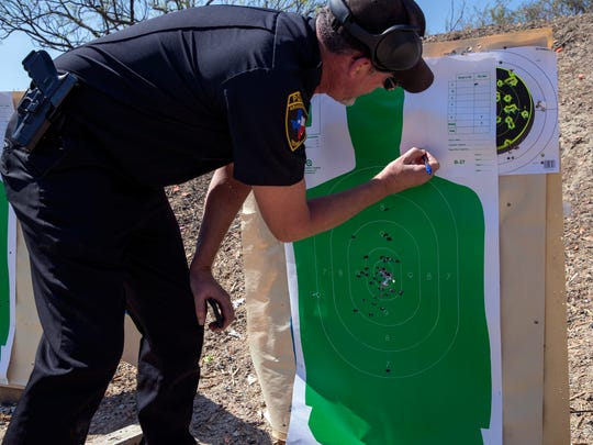 """Lynn Pearce, Aransas Pass Police administrative captain, adds up the holes in a target while teaching a Texas Handgun Licensing Course for Aransas Pass Independent School District staff on Saturday, March 10, 2018, at the Schwenke's Rifle & Pistol Range in Aransas Pass. The Aransas Pass ISD Board of Trustees has not decided whether to allow staff to carry guns on school campuses. """"This class had nothing to do with the decision that the school board is making or not going to make,"""" Pearce said. """"That's up to them. We're just facilitating what we can."""""""