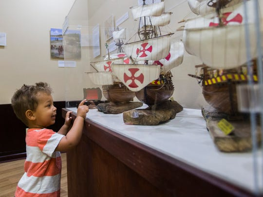 Braxton Sengegal, 2, looks at replica ships at the
