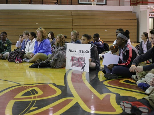 Pineville High Junior J'Nae Hammond holds a sign that