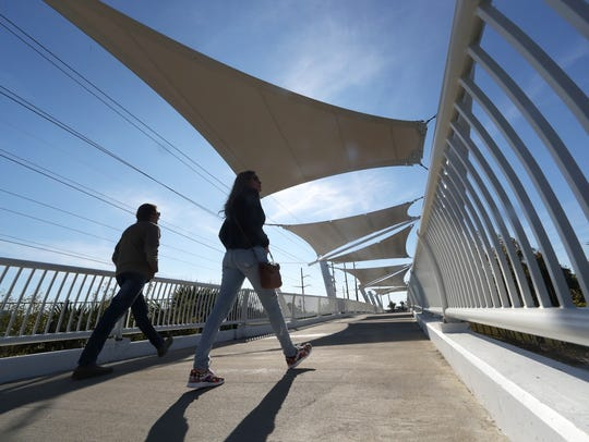 People walk across the pedestrian bridge at Cascades