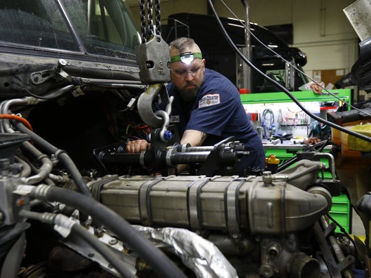Diesel mechanic Jim Howe, 34, of Wausau, prepares to disassemble the head of a truck engine Wednesday, March 7, 2018, at Truck Country in Rothschild, Wis. T'xer Zhon Kha/USA TODAY NETWORK-Wisconsin