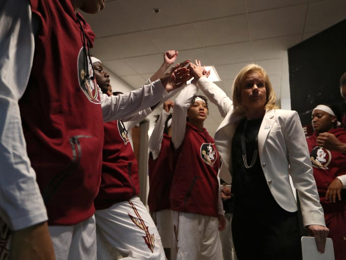 FSU Head Coach Sue Semrau huddles up with her team
