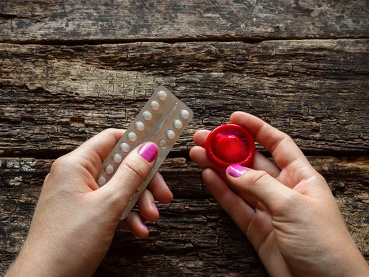 young woman holding a birth control pills and a condom
