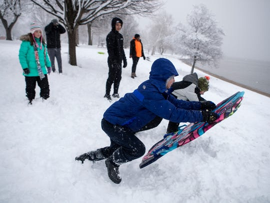 Savannah Anders, center, and Jaydon Buchanan, right, dive to start a sled race Wednesday afternoon at Battery Park.