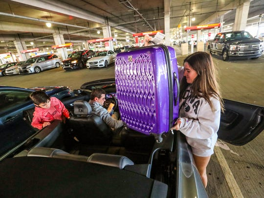 Alyssa Scharkey, 16 of Chicago, puts her bag in the back seat of the convertible as her dad, Michael, gets the car ready to drive and her brother, Michael, 10, looks for a spot to sit. The car rental building at RSW opposite the terminal is a hopping spot this time of year as spring break puts a big demand on rental cars. RSW is known as a car rental hot spot, but during season cars are especially in demand.