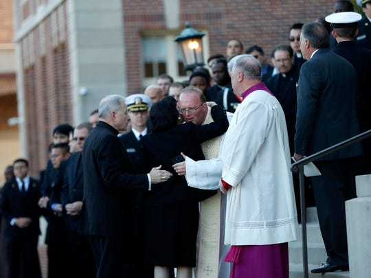 New Orleans Archbishop Gregory Aymond, facing right, escorts Gayle Benson, widow of NFL New Orleans Saints and NBA New Orleans Pelicans owner Tom Benson, as she hugs clergy before his visitation at Notre Dame Seminary in New Orleans, Wednesday.