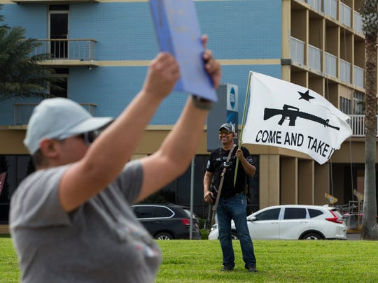 Steve Martinez  stands with a rifle as people march past him during the March for Our Lives rally on Saturday, March 24, 2018 in Corpus Christi.