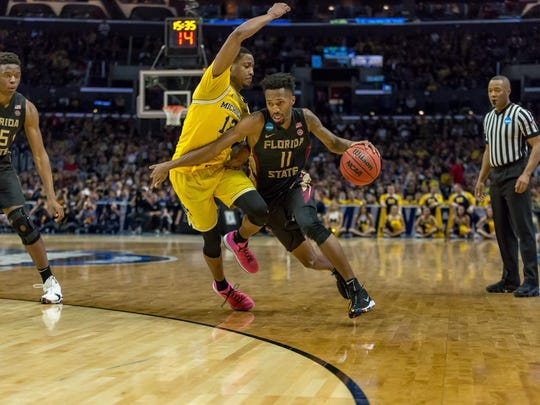 Senior guard Braian Angola drives the ball against a Michigan defender in Florida State's matchup against Michigan in the Elite Eight.