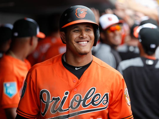 In this March 2, 2018, file photo, Baltimore Orioles' Manny Machado celebrates in the dugout after hitting a 3-run home run off Pittsburgh Pirates relief pitcher Damien Magnifico in the fourth inning of a spring training baseball game in Sarasota, Fla.