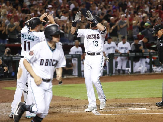 Nick Ahmed high-fives teammates after hitting a three-run home run against the Rockies on Friday.