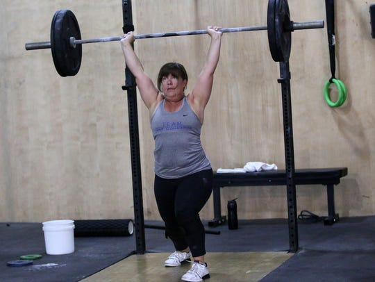 Janine Giovinazzi completes a clean-and-jerk lift while training for an upcoming national competition at Crossfit Estero in Estero on Monday, April 2, 2018. Giovinazzi will compete at the Masters Weightlifting Championship in Buffalo, New York this weekend.