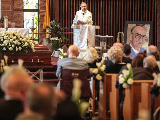 The Rev. Howard Lincoln presides over Jim Houston's funeral service at Sacred Heart Catholic Church in Palm Desert on Thursday.