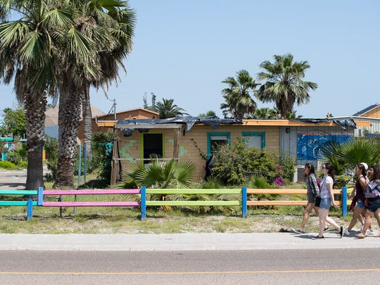 A group of people walk past what was Laughing Horse Lodge on Avenue G in Port Aransas on March 30. The structures were planned for demolition.