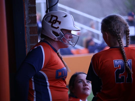 Dickson County catcher Maggie Terrell talks with teammates