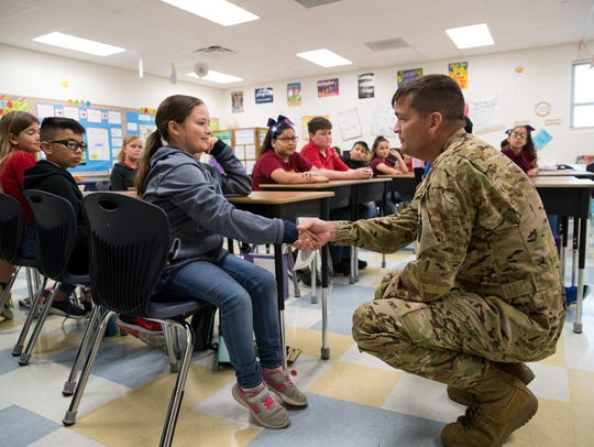 Army pilot Andrew Gardner shakes hands with a fifth-grader
