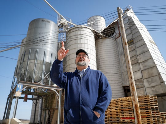 Matt Aultman, a grain salesman and feed nutritionist with Keller Grain & Feed, Inc., speaks beside grain and soybean silos during an interview at their facilities in Greenville, Ohio, Thursday, April 5, 2018, in Greenville. Rural America is struggling under a cloud of uncertainty as the Trump administration escalates a trade dispute with China. The Republican president says he's simply fighting against unfair business practices with a geopolitical rival. But voters in rural America, those who fueled his 2016 presidential victory, say Trump's moves are threatening their livelihoods and forcing some to re-think their politics.
