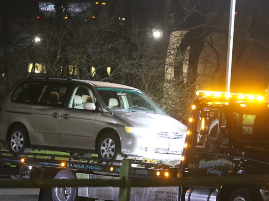 A minivan is towed away from the scene of a death a Seven Hills School.