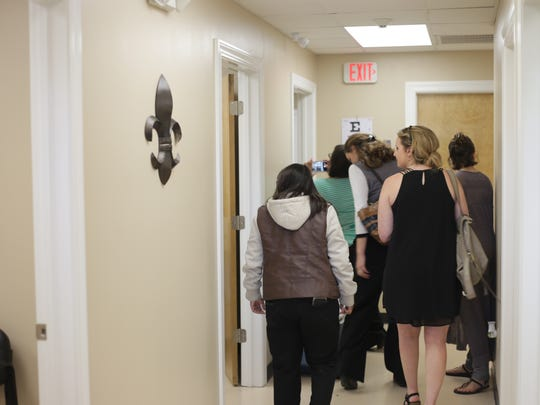 People tour the new school-based clinic at Alexandria Middle Magnet during an open house held Thursday.
