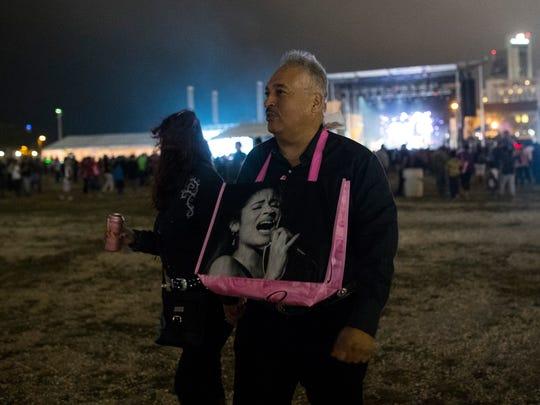 A man walks with a Selena bag around his neck at Fiesta de la Flor on Friday, April 13, 2018.