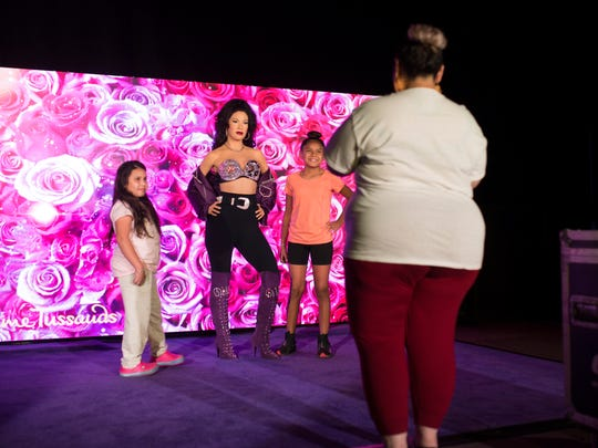 Two girls pose with the Selena wax sculpture People at Fiesta de la Flor on Saturday, April 14, 2018 at the American Bank Center.