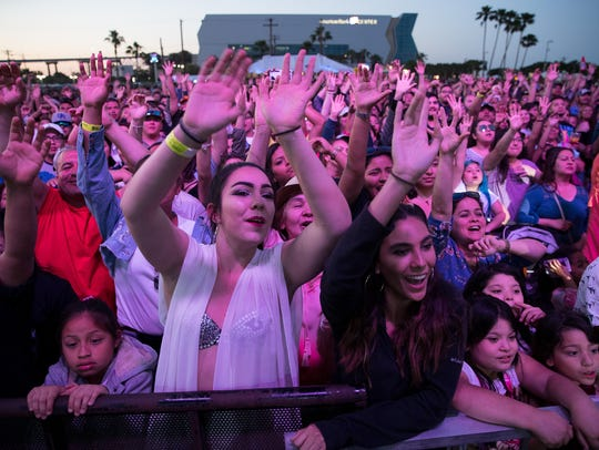 Audience members cheer as they wait for Jenny and the
