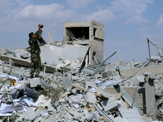 A Syrian soldier films the damage of the Syrian Scientific Research Center which was attacked by U.S., British and French military strikes to punish President Bashar Assad for a suspected chemical attack against civilians.