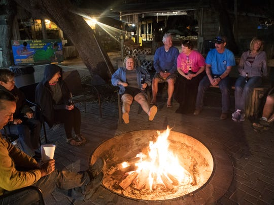 Camp Mack visitors enjoy a cold beverage around a camp fire along the Kissimmee River and chain of lakes. News-Press reporters Chad Gillis and Andrew West stayed at the camp for two nights.