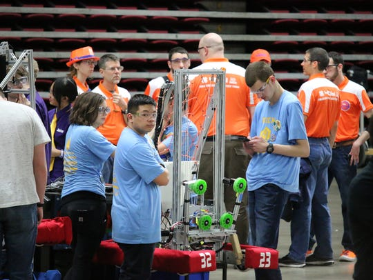 "Members of Robotics of Central Kitsap (ROCK) prepare for a FIRST Robotics Competition tournament earlier this year in Yakima. They include, from left, Lauren Judd, Michael ""Mikey"" Frilles, and Kevin Richmond. The robot's name is ""Rockslide."""