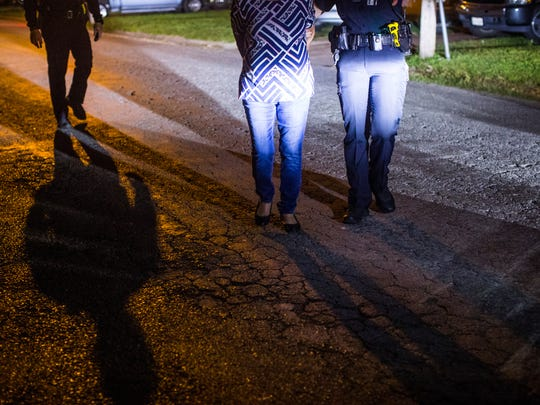 DWI officer Samantha Baldwin takes a suspected drunk driver into custody after field sobriety test on Friday, April 6th, 2018. on Friday, April 6th, 2018.