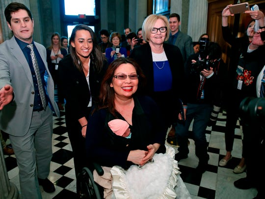 Sen. Tammy Duckworth, D-Ill., carries her baby Maile Pearl Bowlsbey as she heads to the Senate floor to vote, with Sen. Claire McCaskill, D-Mo., at right, on Capitol Hill, Thursday, April 19, 2018 in Washington. (AP Photo/Alex Brandon)
