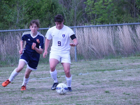 Clarksville Academy's Bradley Burger keeps the ball away from a Nashville Christian defender during the first half of their soccer game Thursday.