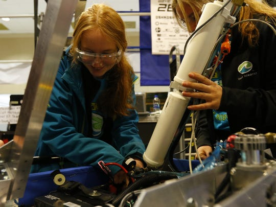 Taylor Payne and Annabelle Wojahn work on the robot in the pit.