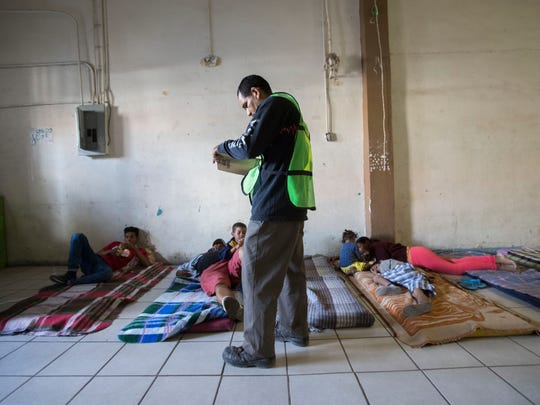 """130 migrants arrived at Hotel de Migrante, a migrant shelter in border city Mexicali from Central America as part of a """"migrant caravan"""" that started in Tapachula, Chiapas, Mexico nearly a month ago The migrants will try to seek asylum in the United States. In this photo a volunteer takes down names of the migrants as they rest before heading to Tijuana as their final destination."""