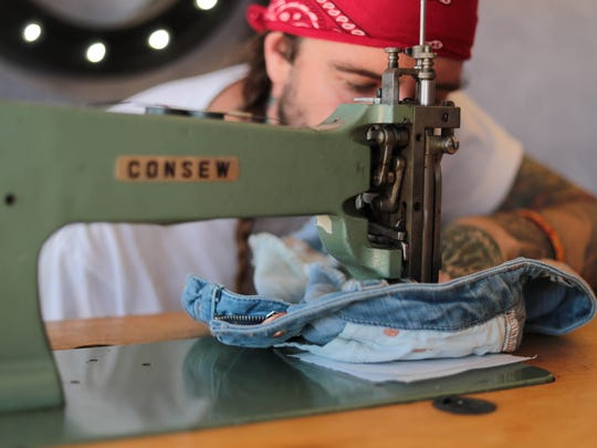 A man embroiders denim at the 2018 Stagecoach music festival.
