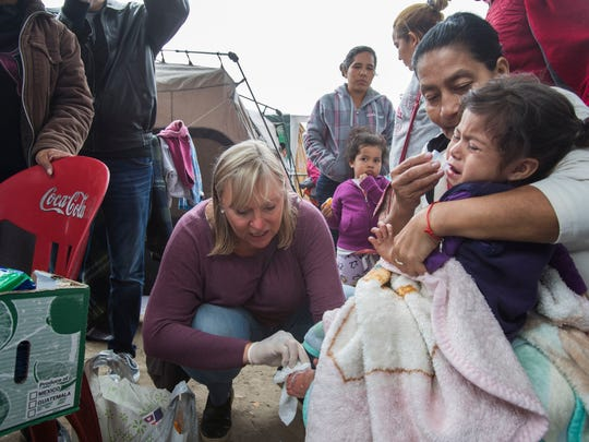 "A migrant child fleeing cartel violence from Michoacan, Miexico is attended by an American pediatric nurse at the ""El Chaparral' U.S. point of entry in Tijuana, Mexico on May 1, 2018."